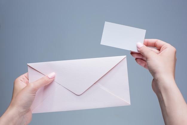 Vrouwelijke handen met envelop tegen grijs