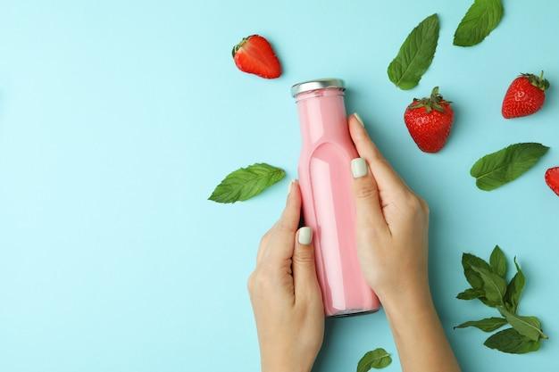 Vrouwelijke handen met fles aardbeienmilkshake op blauwe achtergrond