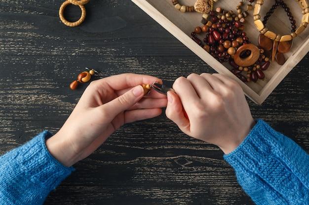 Vrouwelijke handen met gekleurde kralen ketting productie