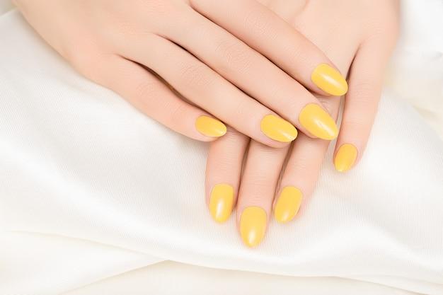 Vrouwelijke handen met gele nagel ontwerp op witte stof oppervlak.