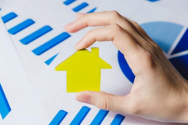 Vrouwelijke handen met gele papier huis