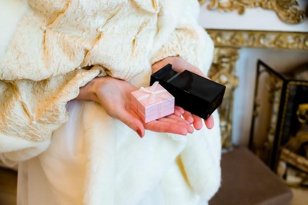 Vrouwelijke handen met geschenkdoos en zwarte parfumfles. roze doos en fles parfum.