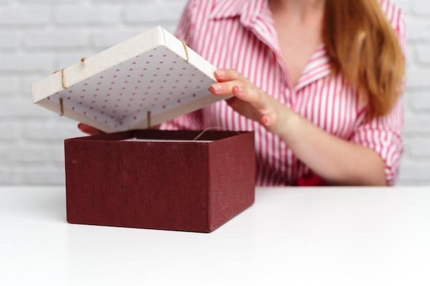 Vrouwelijke handen met geschenkdoos.