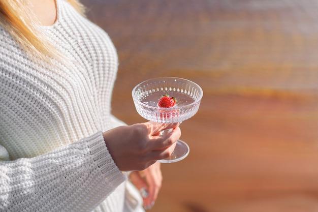 Vrouwelijke handen met glas water met aardbei