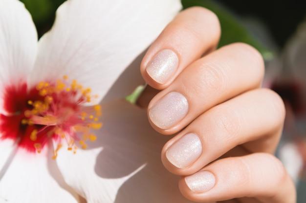 Vrouwelijke handen met glitter manicure.