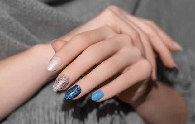 Vrouwelijke handen met glitter nageldesign met grijze wollen sjaal.
