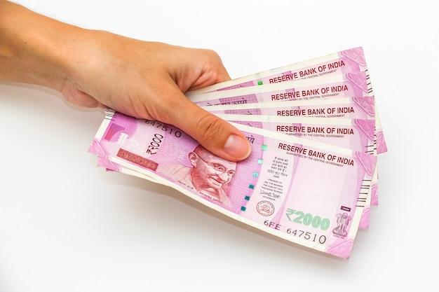 Vrouwelijke handen met gloednieuwe 2000 indiase roepies bankbiljetten.