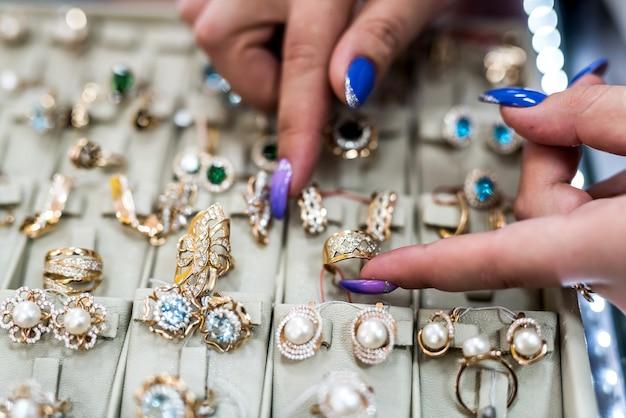 Vrouwelijke handen met gouden sieraden in winkel close-up