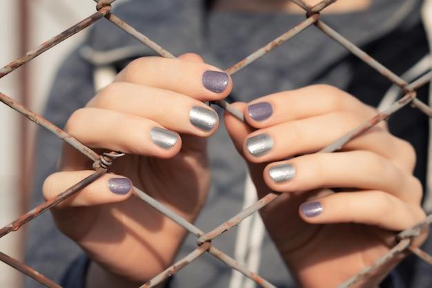 Vrouwelijke handen met grijze glitter nagel ontwerp.