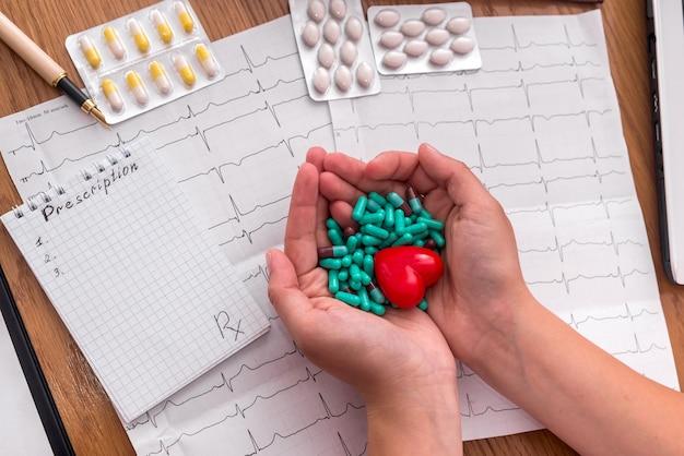 Vrouwelijke handen met groene capsules en rood hart