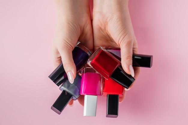 Vrouwelijke handen met heldere nagellakken.