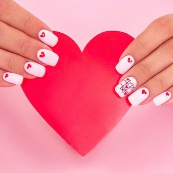 Vrouwelijke handen met het witte ontwerp van manicureharten