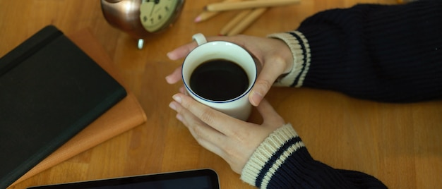 Vrouwelijke handen met hete koffiekopje op houten werktafel met briefpapier en klok