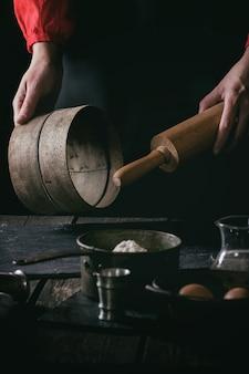 Vrouwelijke handen met houten deegrol en zeef
