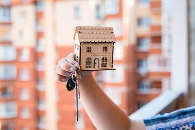 Vrouwelijke handen met houten huismodel en sleutels