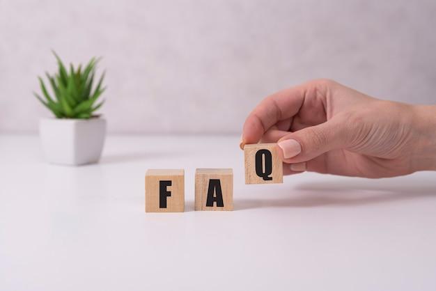 Vrouwelijke handen met houten kubussen met de tekst faq, veelgestelde vragen