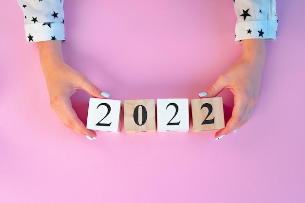Vrouwelijke handen met houten kubussen van het jaar 2022 boven roze