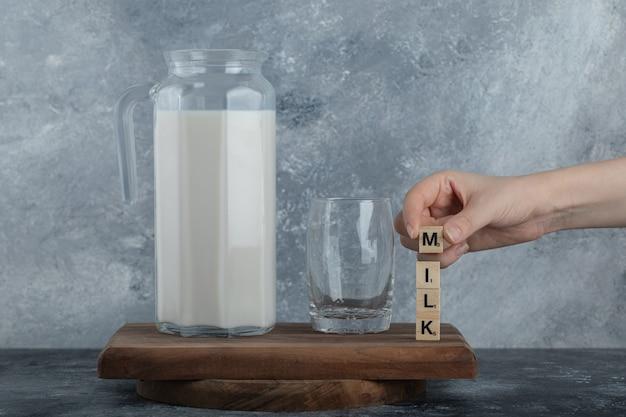 Vrouwelijke handen met houten letters met verse melk.