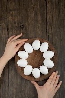 Vrouwelijke handen met houten plank met rauwe eieren op houten oppervlak.