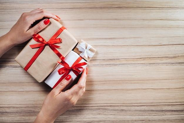 Vrouwelijke handen met kerst geschenkdozen versierd met satijnen linten op houten achtergrond