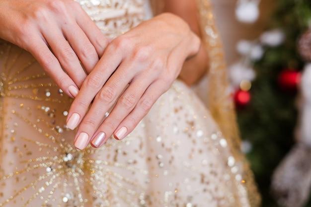 Vrouwelijke handen met kerst-nieuwjaar nageldesign. naakt beige nagellak manicure