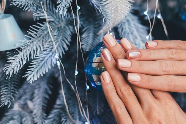 Vrouwelijke handen met kerst-nieuwjaar nageldesign. nude beige nagellak manicure, één vinger glanzend gouden brons