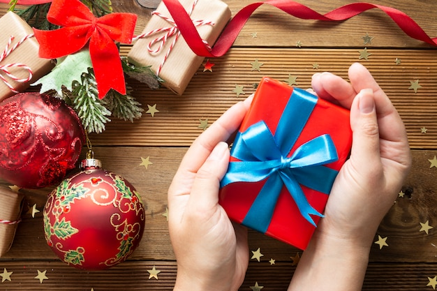 Vrouwelijke handen met kerstcadeau, rode geschenkdoos. verpakkend een doos op houten achtergrond.
