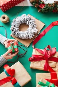 Vrouwelijke handen met kerstcadeaus en krans