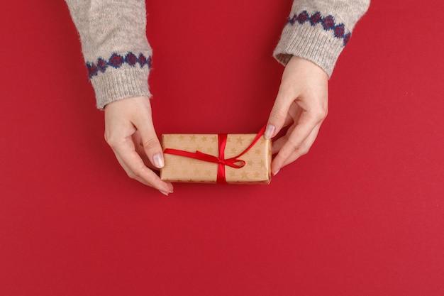 Vrouwelijke handen met kerstmisgift op rode achtergrond, hoogste mening, exemplaarruimte