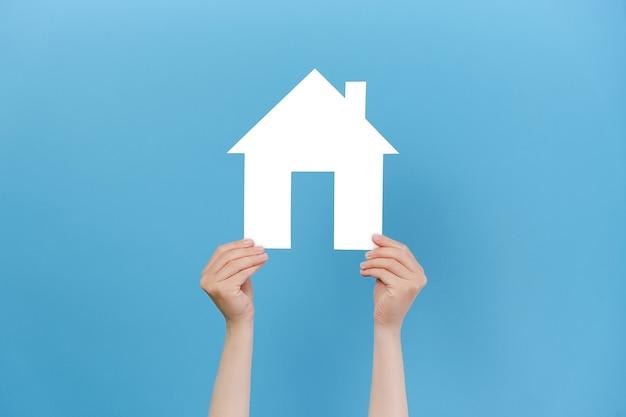 Vrouwelijke handen met klein papieren huis