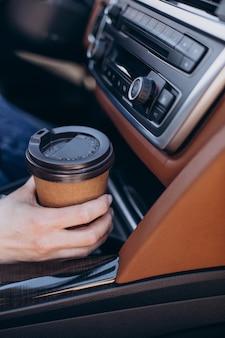 Vrouwelijke handen met koffiekopje in de auto