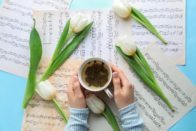 Vrouwelijke handen met kop warme koffie op tafel met notitieblaadjes en bloemen