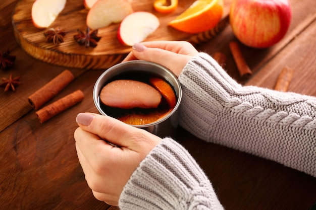 Vrouwelijke handen met kopje heerlijke glühwein op houten tafel