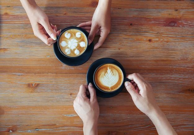 Vrouwelijke handen met kopjes koffie op rustieke houten tafel achtergrond