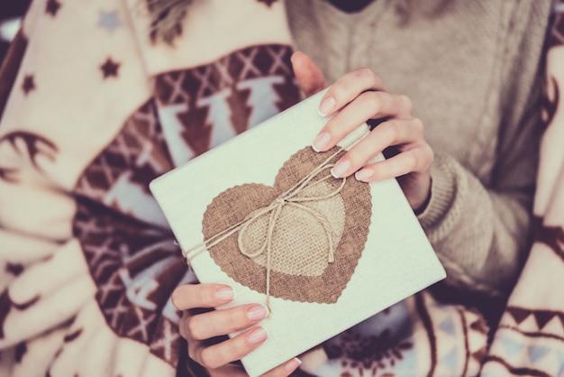 Vrouwelijke handen met kraft geschenkdoos met hart.