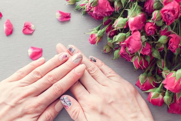 Vrouwelijke handen met kunst nagel manicure en kleine roze rozen