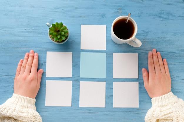 Vrouwelijke handen met lakens voor het plannen van de week en koffie op een blauwe tafel