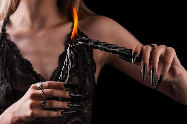 Vrouwelijke handen met lange nagels houden brandende kaarsen, hekserij op halloween.