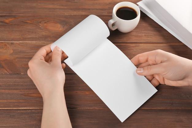 Vrouwelijke handen met lege brochure op houten