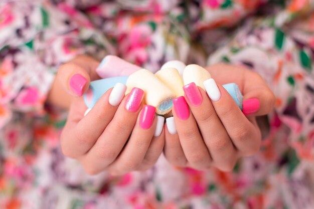 Vrouwelijke handen met manicure met marshmallow