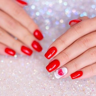 Vrouwelijke handen met manicurespijkers, rode gellak, hartontwerp