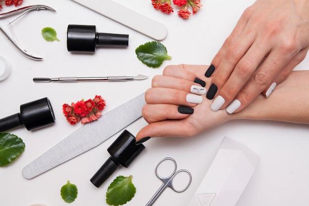 Vrouwelijke handen met mat zwart-wit manicure en tools
