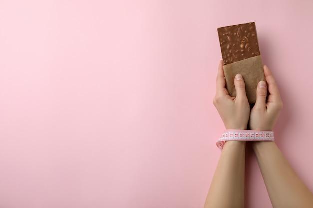 Vrouwelijke handen met meetlint houden chocoladereep geïsoleerd