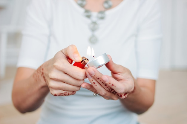 Vrouwelijke handen met mehendi lichte drijvende kaars