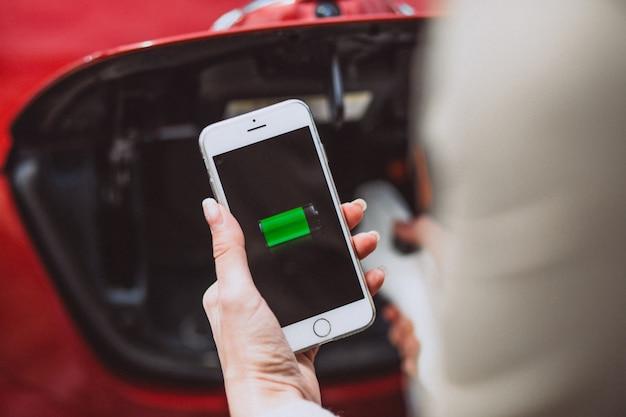 Vrouwelijke handen met mobiele batterij die elektroauto laadt