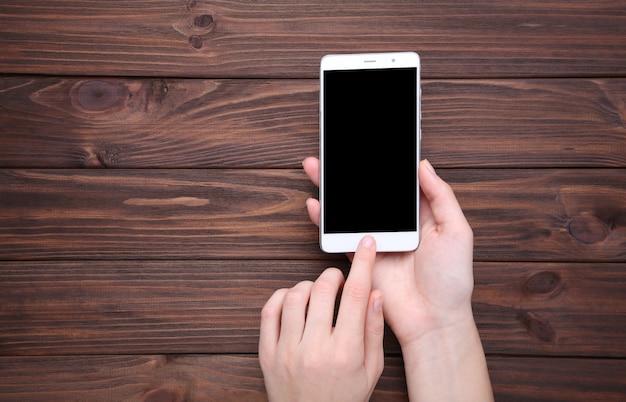 Vrouwelijke handen met mobiele telefoon met leeg scherm
