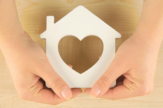 Vrouwelijke handen met model van huis op houten tafel