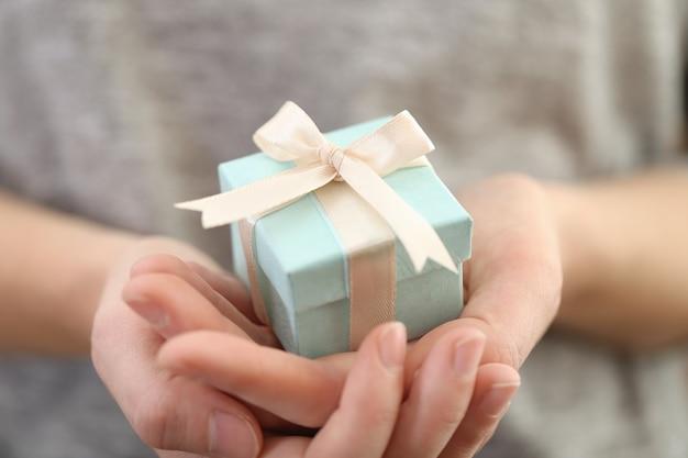 Vrouwelijke handen met mooi klein cadeautje omwikkeld met satijnen lint.