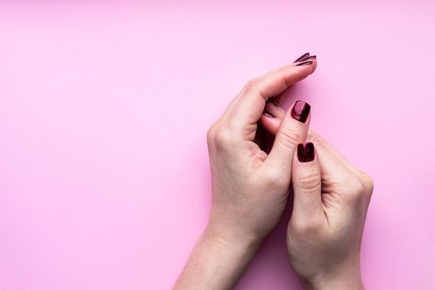 Vrouwelijke handen met mooie manicure - donkerrode glinsterende nagels op roze achtergrond met kopie ruimte