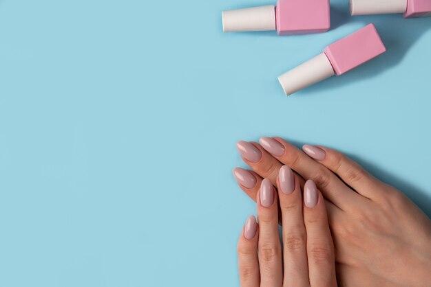 Vrouwelijke handen met mooie manicure en flessen met roze gellak